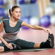 Woman doing stretching fitness exercise at sport gym. Yoga