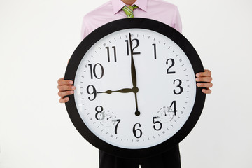 Young businessman with giant clock