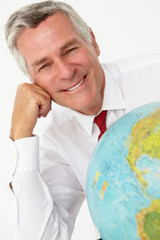 Senior businessman with globe
