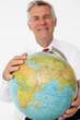 Senior businessman holding globe