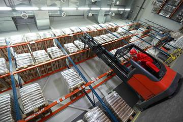 Worker   on   forklift loader loading sacks in warehouse