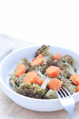 Brocoli con zanahoria en plato sobre fondo blanco