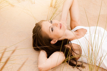 Frau liegt in Dünen
