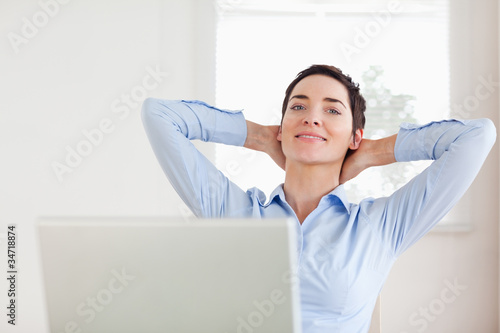 Short-haired relaxed businesswoman with a laptop looking into th
