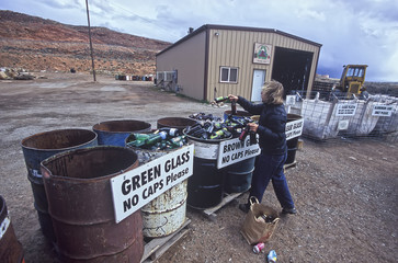 Woman recycles glass bottles.