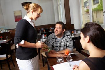 Kellnerin im Restaurant empfiehlt Wein