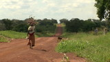 woman walking down dirt road in rural africa