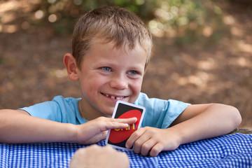 Jeune garçon jouant aux cartes : Petit tricheur !