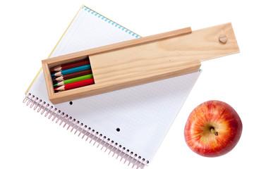 lápices, cuaderno y manzana
