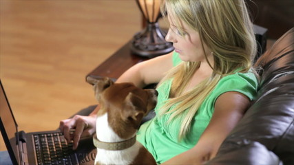 Pretty girl with laptop and dog looks up and smiles