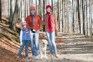 Autumn - Family with dog walking in autumn forest