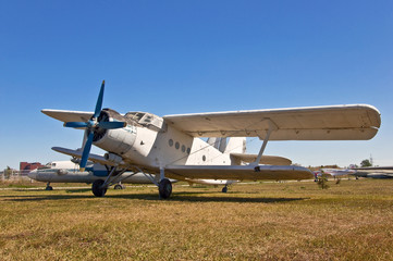 old russian airplane on grass and blue sky background