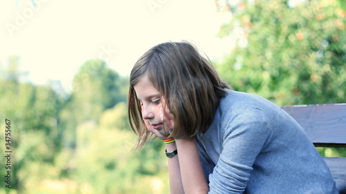 Sad teenage girl sitting on bench outdoors, dolly shot