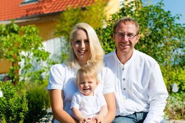 Familie mit Baby vor Haus