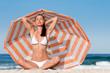 Frau sitzt vor Sonnenschirm