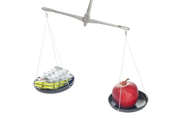 Laboratory balance with pill and apple