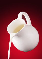 pitcher of milk on a red background