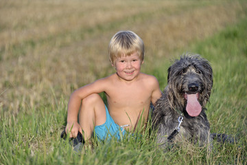 Kind mit Hund auf Wiese