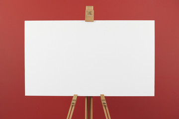 Artist's canvas on easel, red background