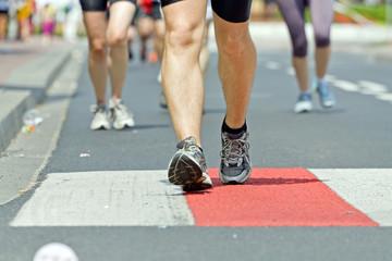 People running in marathon on city street