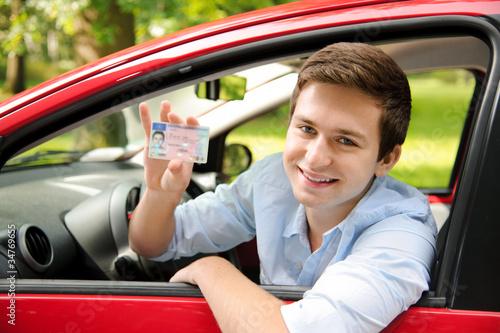 Leinwanddruck Bild Jugendlicher mit neuem Auto und Führerschein