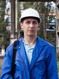 Young handsome man constructor in white hardhat and blue uniform poster