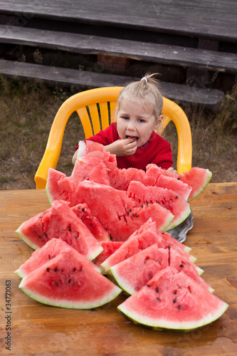 Little child eating watermelon. Many red slices on table