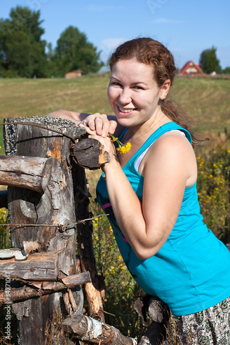 One young Caucasian Russian woman near village fence