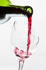 Red wine pouring to the broken glass