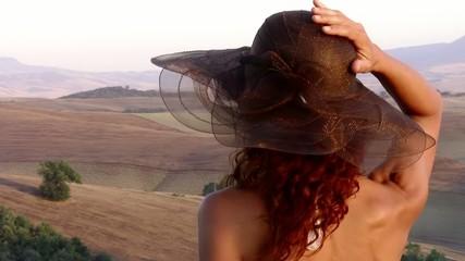 paesaggio di toscana e donna con un cappello