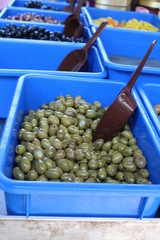A mass of green olives on display at a market