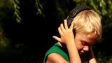 Boy in earphone listens music and dancing