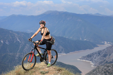 A young female posing with a mountain bike