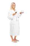 Young woman in bathrobe holding a coffee cup and mobile phone