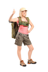 Smiling woman with backpack givimh thumb up