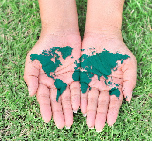 Map of the world in your hands with green grassy background