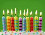 Fototapety Ten colorful candles on green background