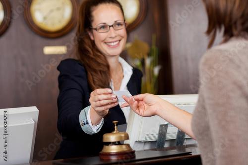 rezeptionistin überreicht einem gast die karte - 34806223