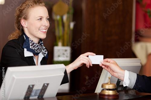 lächelnde rezeptionistin überreicht karte