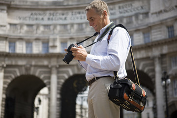 A middle-aged man looking at his camera