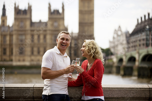 A middle-aged couple in front of Houses of Parliament, drinking