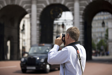 A middle-aged man photographing Admiralty Arch