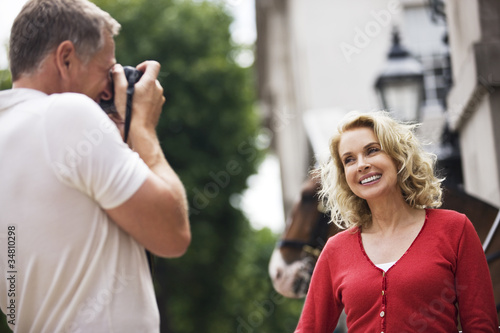 A middle-aged man taking a photograph of his partner