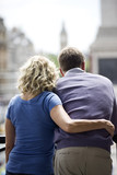 A middle-aged couple standing by Trafalgar Square, rear view