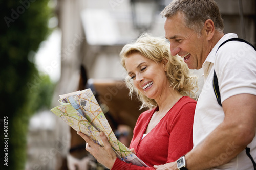 A middle-aged couple looking at a map, smiling