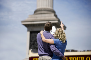 A middle-aged couple standing in front of Nelson's column