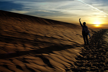 People rising arm in the desert in the evening