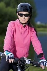 young caucasian grl in helmet riding bike outdoor
