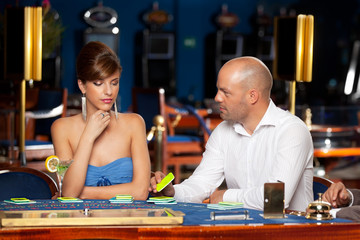 flirting couple playing cards in a casino