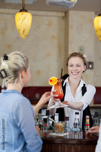frau bekommt cocktail in der bar